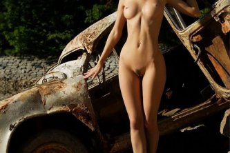 Posing in front of a rusty old car